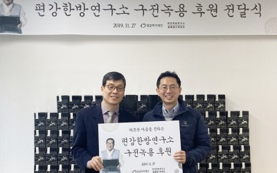 안산시장애인복지관 박상호관장과 편강한방연구수 김창수 부장이 후원 판넬을 들고 서있는 모습