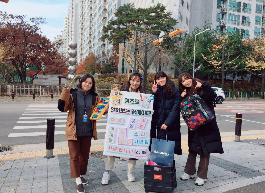 장애인 인식개선 캠페인 제시어 판넬과 선물을 들고 있는 4명의 직원들이 모습이 담긴 사진