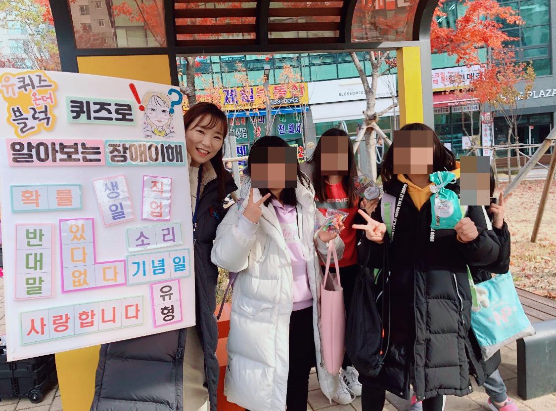 제시어가 적혀 있는 판넬을 든 직원과 문제를 맞춰 선물을 받은 4명의 여학생 모습이 담긴 사진이며, 초등학생들의 얼굴은 모자이크 처리가 되어 있다.