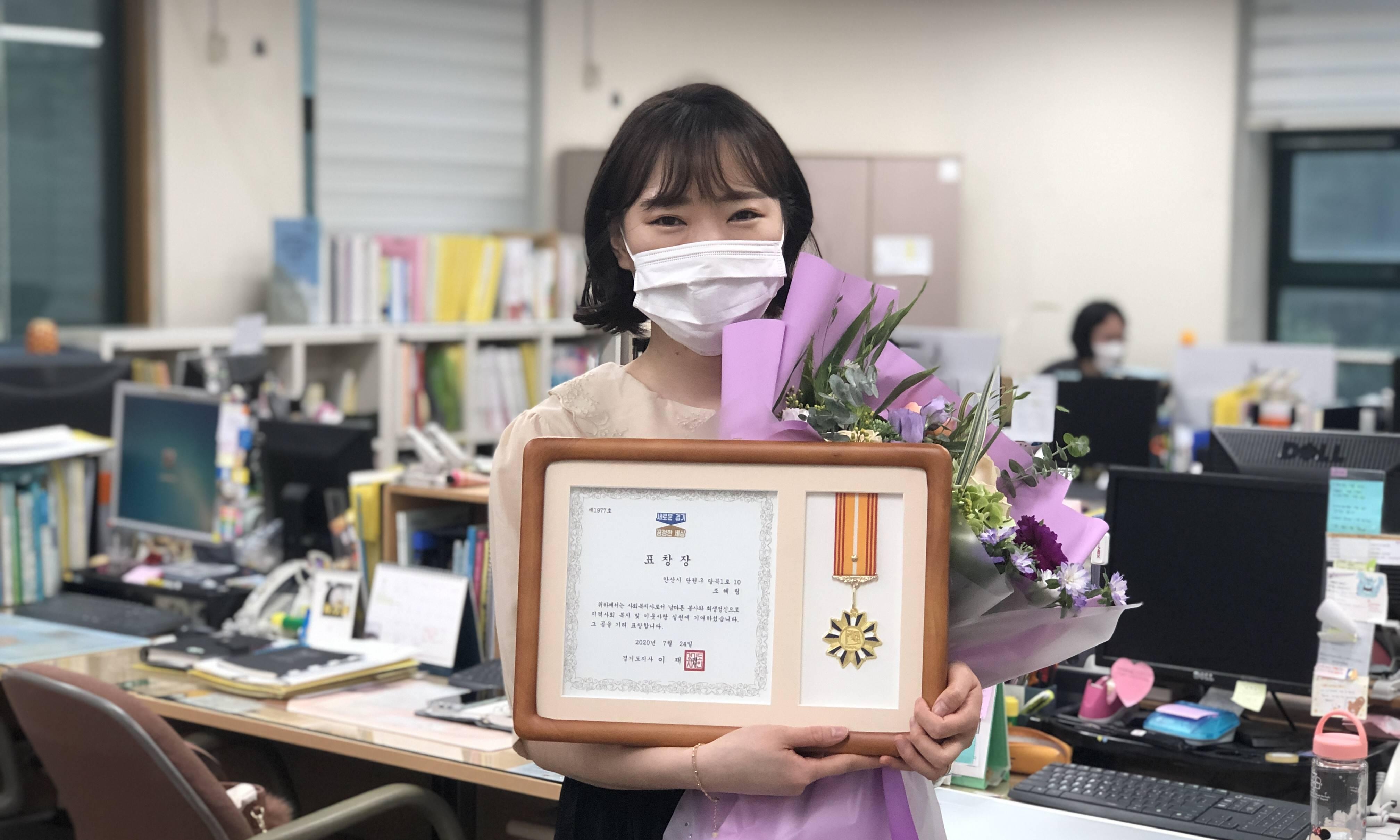 수상자(조혜림 대리)가 상패와 꽃다발을 들고 기념사진을 촬영하는 모습