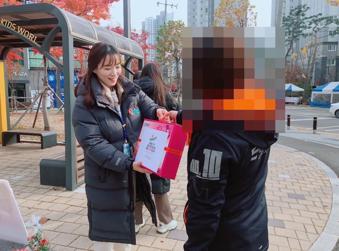 정답을 맞춘 주민에게 선물을 전달하는 모습의 사진