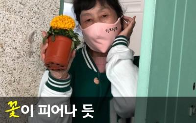 [사진1] '꽃이 피어나 듯 나눔의 마음이 피어나다.'라는 문구와 함께 현관에서 꽃을 들고 있는 여자의 모습이 담긴 사진